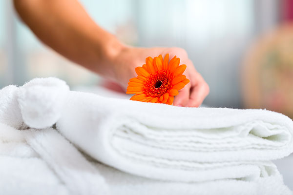 White towel with orange flower on top