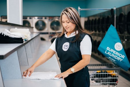 laundromat attendant doing fluff and fold laundry service